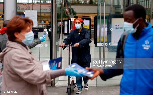 Volunteer distributes face masks and leaflets to commuters in front of the Gare du Nord train station in Paris on April 29 on the 44th day of a...