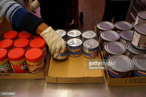 A volunteer distributes food at CAMBA's Beyond Hunger Emergency Food Pantry on February 18 2014 in the Brooklyn borough of New York City The...