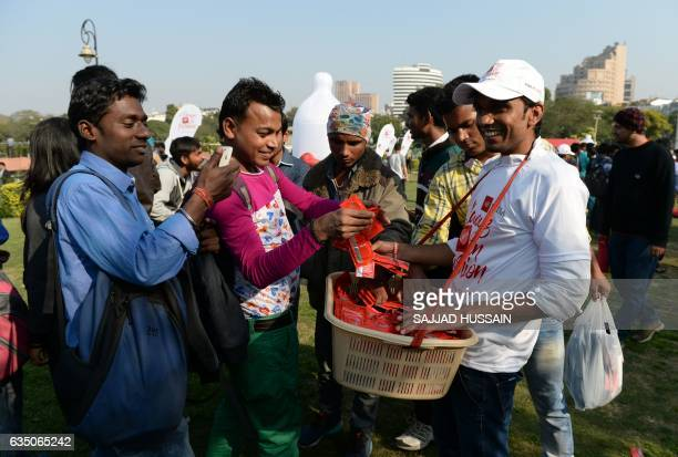 A volunteer distributes free condoms during an event to mark International Condom Day in New Delhi on February 13 2017 The event was organised by...