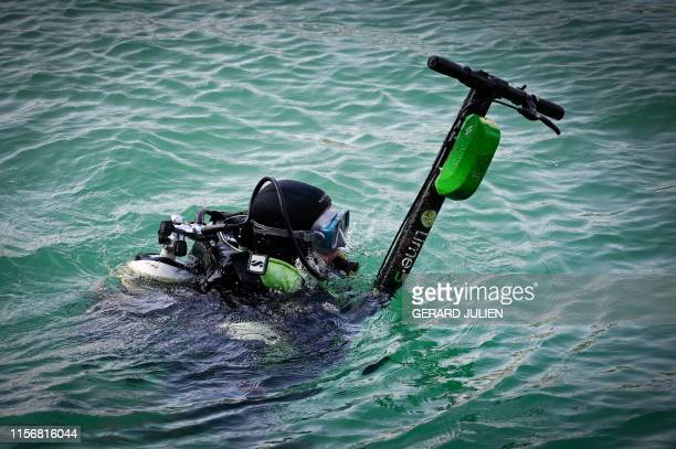 TOPSHOT A volunteer diver swims with an escooter as he recovers escooters thrown into the seawater along the Marseille's coast southeastern France on...