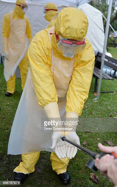 A volunteer doctor who will travel to West Africa to help care for Ebola patients disinfect hands during training offered by the German Red Cross on...