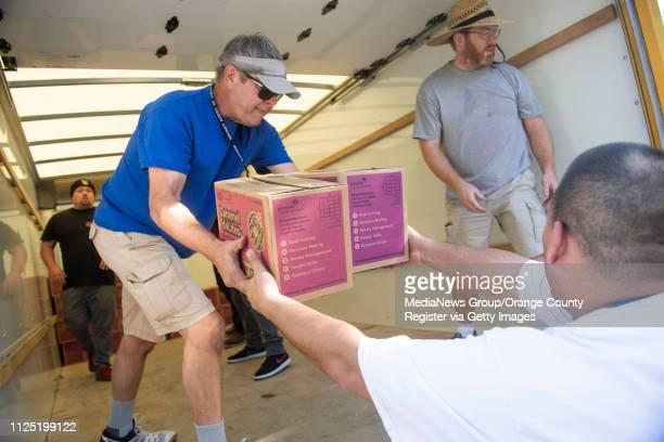 Volunteer Don Evans of Fullerton left helps stack Caramel deLites in the back of a moving truck part of a 348 case order for Girl Scout Troop 3434...