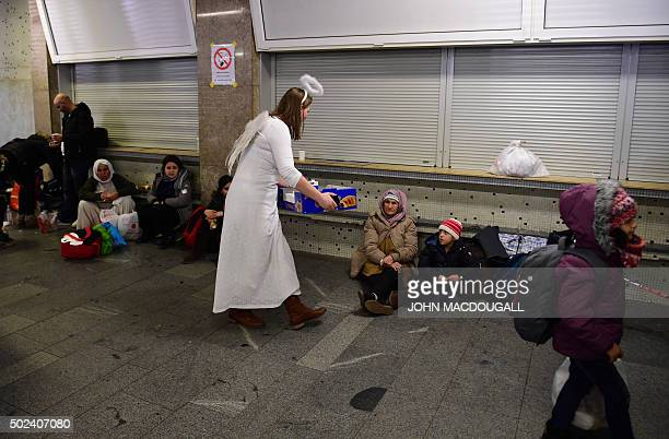 A volunteer dressed in an angel outfit offers hot tea to people as some 200 asylumseekers arrived by train at the Schoenefeld train station near...