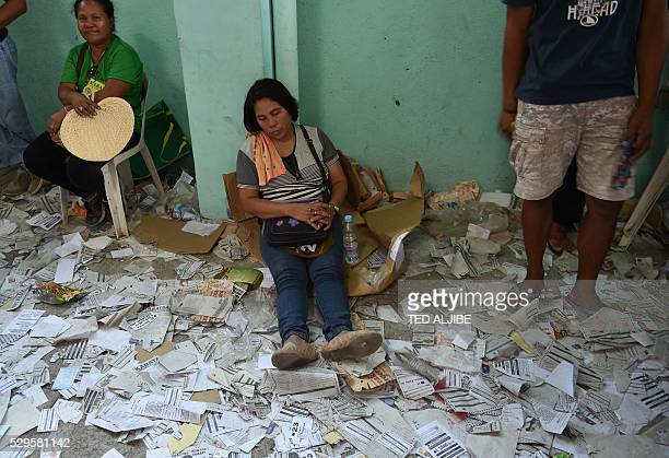 A volunteer election worker takes a rest amongst posters and sample ballots during the presidential election in a slum community in Manila on May 9...
