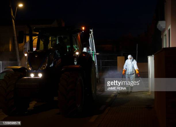 Volunteer farmer uses his tractor to carry out a disinfection in the town of Sant Jordi, on the Balearic island of Mallorca on April 10 during a...
