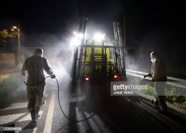 Volunteer farmers use their tractor to carry out a disinfection in the town of Sant Jordi, on the Balearic island of Mallorca on April 10 during a...
