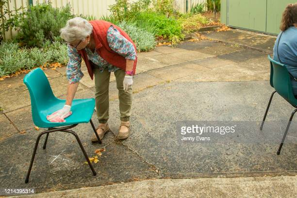 Volunteer Felicity Baker wipes a seat at St Paul's Anglican Church in Burwood on March 24 2020 in Sydney Australia The Parish Pantry provides food...
