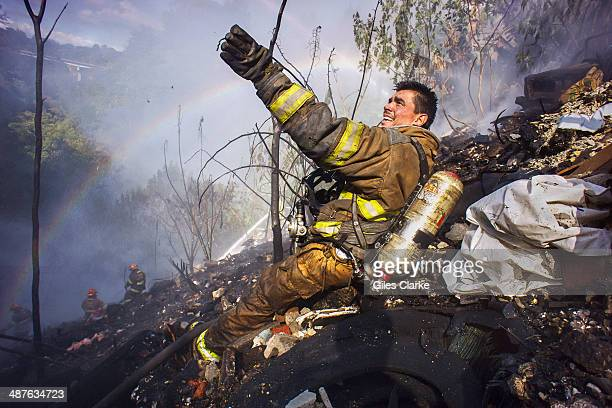 A volunteer firefighter calls out for water during an intense and grueling canyon fire January 20 2014 in Guatemala City Guatemala The bomberos...