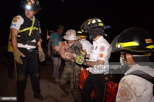 TOPSHOT A volunteer firefighter carries a child after the eruption of the Fuego Volcano in El Rodeo village Escuintla department 35 km south of...