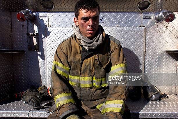 A volunteer firefighter rests after a grueling and intense canyon fire January 20 2014 in Guatemala City Guatemala The bomberos voluntarios are a...