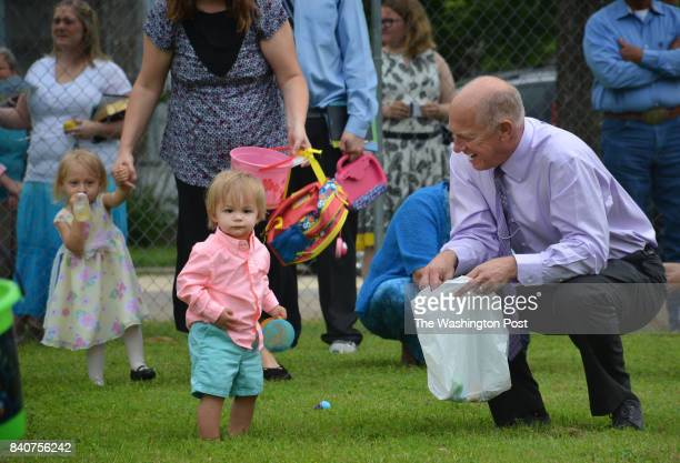 Volunteer firefighter Robby Payne president of the only funeral home helps his grand nephew Finn at the Easter egg hunt sponsored by the First...