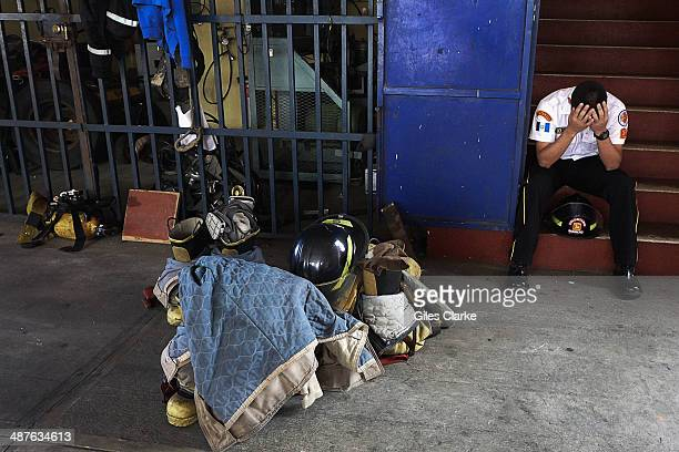 A volunteer firefighter takes a brief break from his grueling schedule December 11 2013 in Guatemala City Guatemala The bomberos voluntarios are a...
