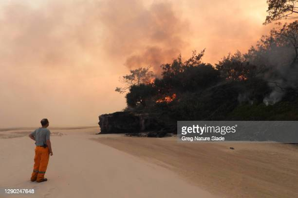Volunteer fire-fighter watches a slow burning fire move along the beach on December 07, 2020 in Fraser Island, Australia. Queensland Fire and...