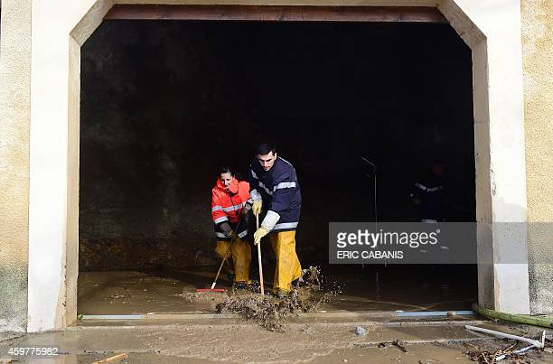 Volunteer firefighters clean a building damaged by flooding from the Berre river in PorteldesCorbieres southern France on December 1 2014 Parts of...