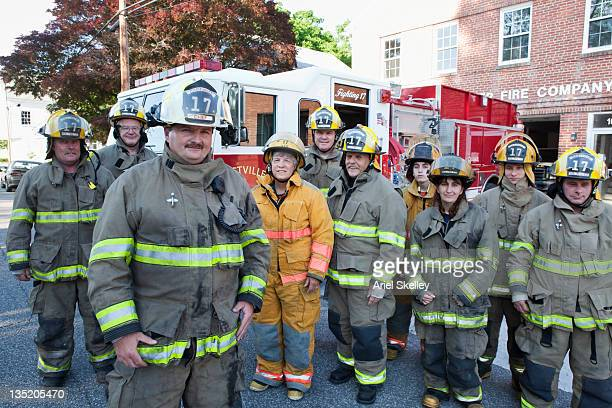 volunteer firefighters posing at fire house - fire station stock photos and pictures