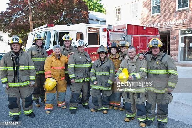 volunteer firefighters posing outside fire house - fire station stock photos and pictures