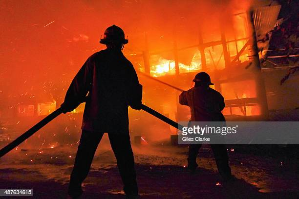 Volunteer firefighters respond to a house fire December 11 2013 in Guatemala City Guatemala The bomberos voluntarios are a volunteer fire fighting...