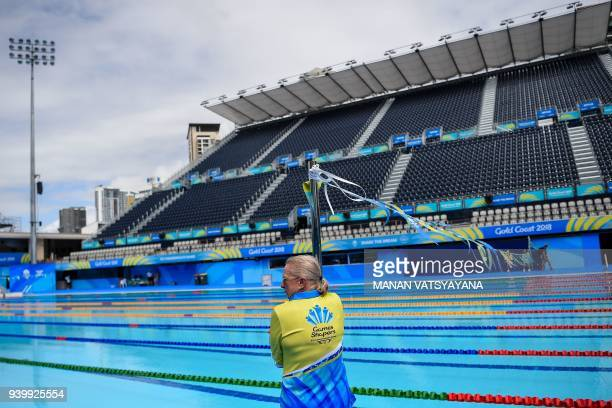 A volunteer fixes a pole at the Optus Aquatic centre ahead of the 2018 Gold Coast Commonwealth Games on March 30 2018 / AFP PHOTO / Manan VATSYAYANA