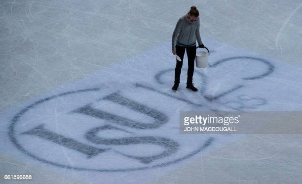 A volunteer fixes the ice next to an International Skating Union logo during the ice dance/short dance event at the ISU World Figure Skating...