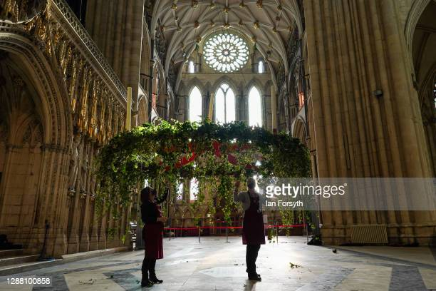Volunteer flower arrangers Liz Freeman and Mandy Barker make finishing touches to the Advent wreath before it is raised into its traditional position...