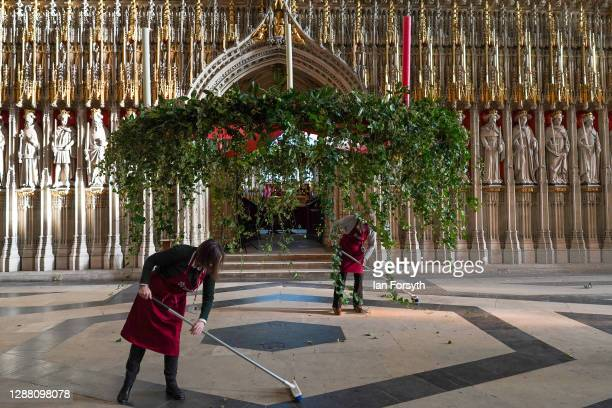 Volunteer flower arrangers Liz freeman and Mandy Barker sweep up after making finishing touches to the Advent wreath before it is raised into its...