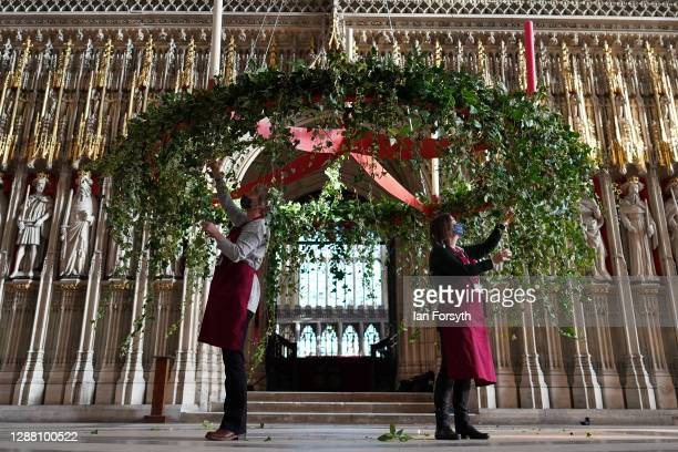 Volunteer flower arrangers Mandy Barker and Liz Freeman make finishing touches to the Advent wreath before it is raised into its traditional position...