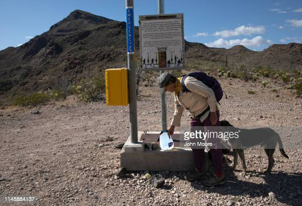 A volunteer for the humanitarian aid group No More Deaths places a bottle of water near a desert rescue beacon on May 11 2019 in Ajo Arizona The US...