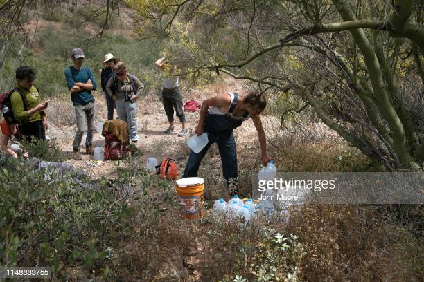 A volunteer for the humanitarian aid organization No More Deaths delivers water along a trail used by undocumented immigrants in the desert on May 10...