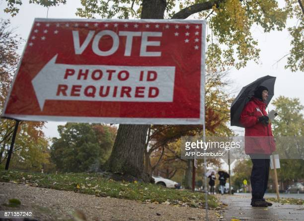 A volunteer for the Independent political party stands outside a polling station waiting to speak to voters in Arlington Virginia on November 7 2017...