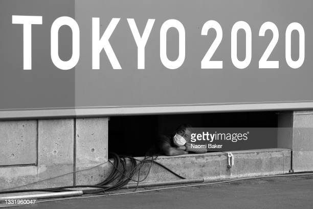 Volunteer for Tokyo 2020 looks on through a gap in the stadium during the Women's Football Semifinal match between USA and Canada at Kashima Stadium...