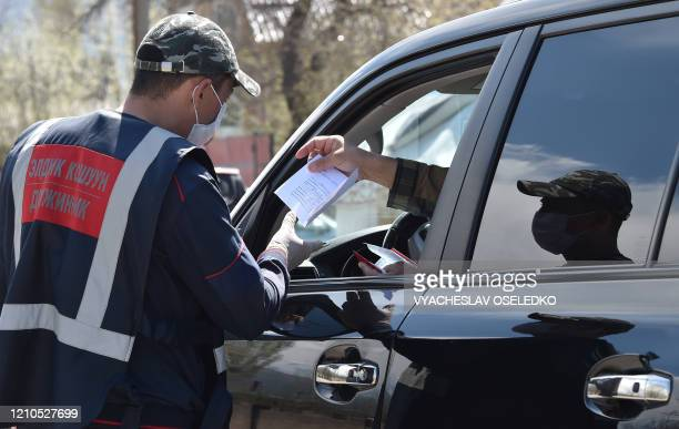 Volunteer from a nearby settlement checks a driver's documents at a checkpoint set up in the village of Koy-Tash, some 20 kilometres from Bishkek, as...