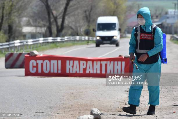 Volunteer from a nearby settlement disinfects a road at a checkpoint set up in the village of Baytik, some 20 kilometres from Bishkek, as the city is...