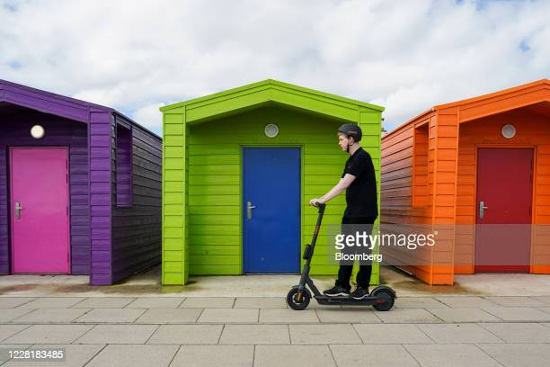 Volunteer from Hartlepower, a charging partner for Ginger, demonstrates an e-scooter during a trial of rental e-scooters by Ginger Teleporter Ltd.,...