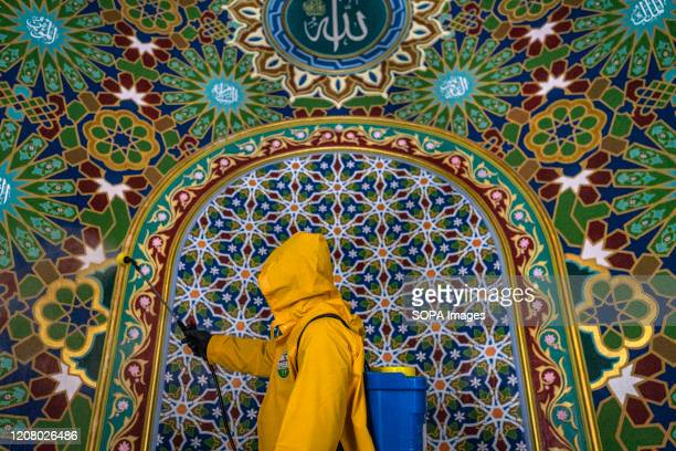 Volunteer from Prevention Task Force for COVID-19 Indonesia sprays disinfectants at Baiturrahman Grand Mosque as a preventive measure against the...