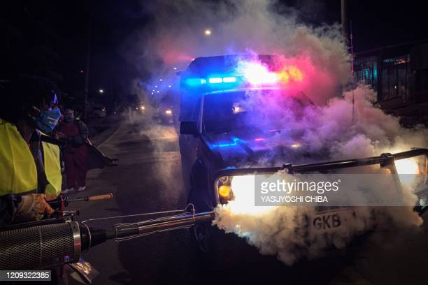 Volunteer from Sonko Rescue Team, an NGO privately funded by Nairobi Governor Mike Sonko, fumigates a police car to curb the spread of COVID-19...