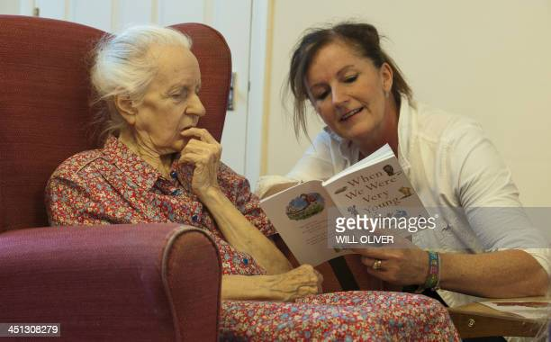 A volunteer from the 'Kissing it Better' charity read poems on October 29 2013 to a resident of a retirement home in Stratford upon Avon who has been...