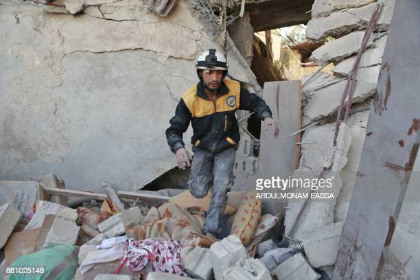 TOPSHOT A volunteer from the Syrian civil defence known as the White Helmets searches the rubble of a building following a reported air strike in the...