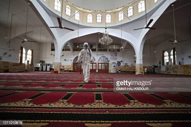 A volunteer from the Violet organisation disinfects a mosque in Syria's northwestern city of Idlib on April 25 from coronavirus during the Muslim...