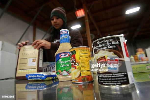 Volunteer Georgelyn Taeza packs boxes of food for needy families at the Alameda County Community Food Bank December 18 2008 in Oakland California As...