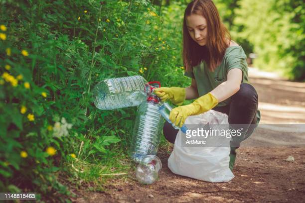 volunteer girl collects garbage - plastic bottles in spring or summer outdoors - environmentalist stock pictures, royalty-free photos & images