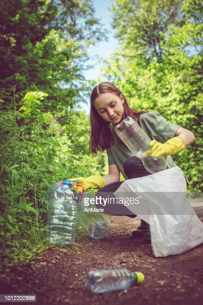 volunteer girl collects plastic bottles outdoors - recycling stock pictures, royalty-free photos & images