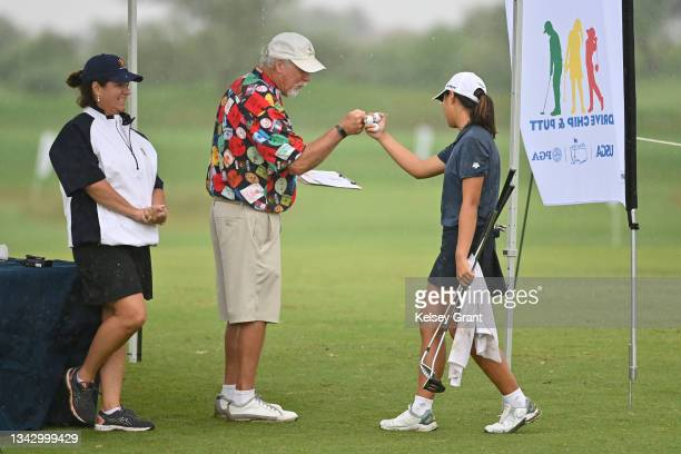 Volunteer gives a competitor a fist bump during the 2021 Drive, Chip and Putt Regional Qualifier at TPC Scottsdale on September 26, 2021 in...