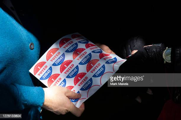 """Volunteer gives an """"I VOTED TODAY"""" sticker to a woman after she cast her early voting ballot at the A. B. Day School polling location on October 17,..."""