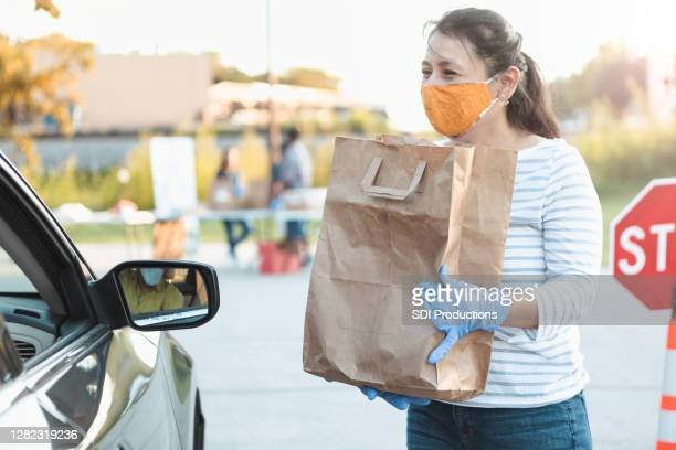 volunteer gives out food during food drive - food bank stock pictures, royalty-free photos & images