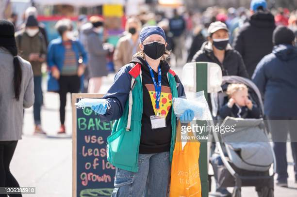 Volunteer gives out free face masks at Union Square Greenmarket amid the coronavirus pandemic on March 10, 2021 in New York City. It has been one...