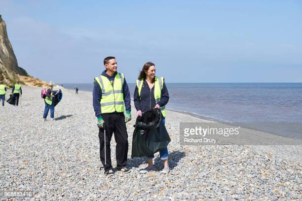volunteer group cleaning beach - selfless stock pictures, royalty-free photos & images