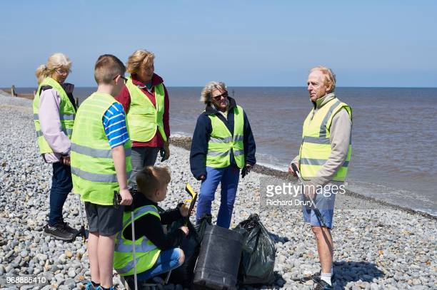 volunteer group gathering at end of beach cleaning session - selfless stock pictures, royalty-free photos & images