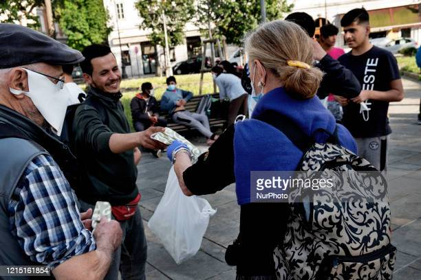 Volunteer group of citizens provid masks to some migrants to prevent the spread of the Coronavirus outside the train station of the city of Trieste....