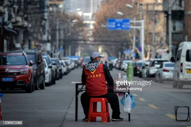 Volunteer guards the temporary wall blocking a road in Wuhan in central China's Hubei province Thursday, March 12, 2020.- PHOTOGRAPH BY Feature China...