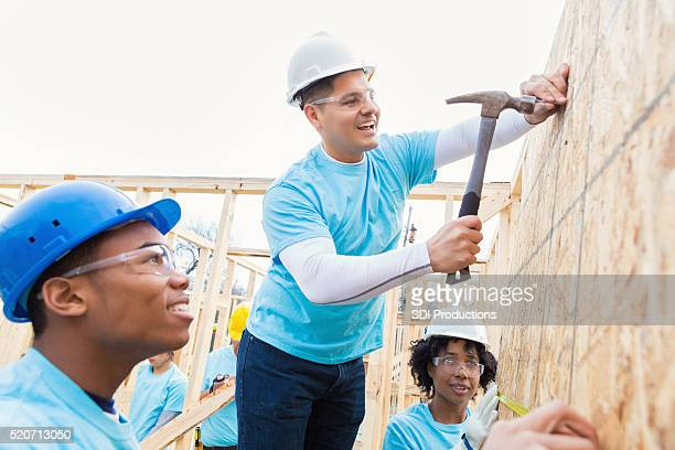 Volunteer hammers nail in wall at charity home worksite